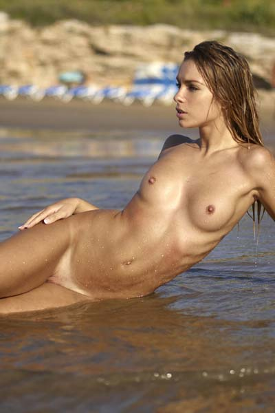 Stunning Amber dips her nude body in the sea