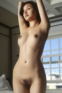 Adoring Eden is posing on the bed showcasing her firm nicely shaped tits and her hairy vagina