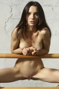 Sexy slender babe poses naked and stretches her petite body on the parallel bars
