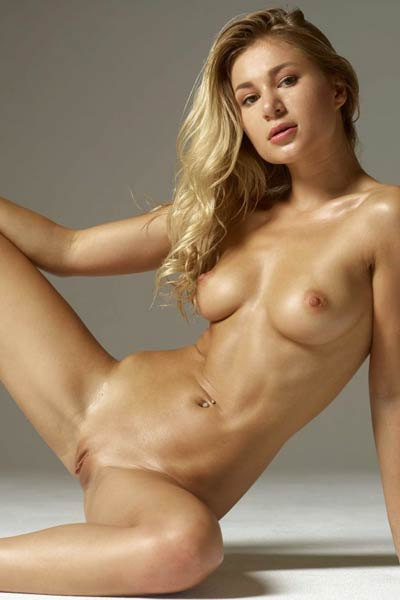 Blonde bombshell poses seductively and bares her big tits and meaty pussy