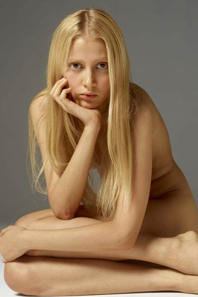 Blonde honey with her seductive eyes poses naked and displays her sexy petite body