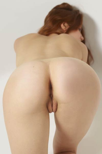Redhead sweetie gently strips down her pink lingerie and flaunts her shaved pussy and pale breasts