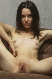 Playful young Olivia gives us a glint of her love holes as she poses naked on the armchair
