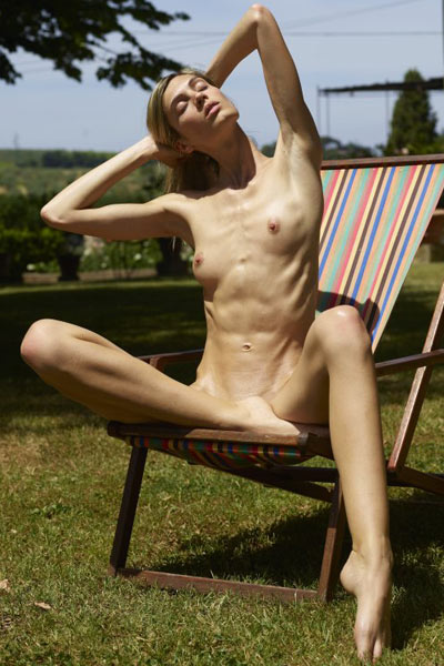 Stunning blonde chick with amazing slender body poses naked on the sun