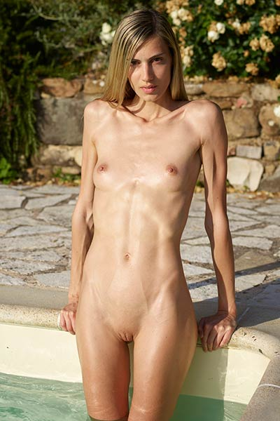 This skinny babe waits for you by the pool completely naked