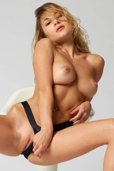 Curly blonde shows off her gorgeous body as she sensually poses on the chair