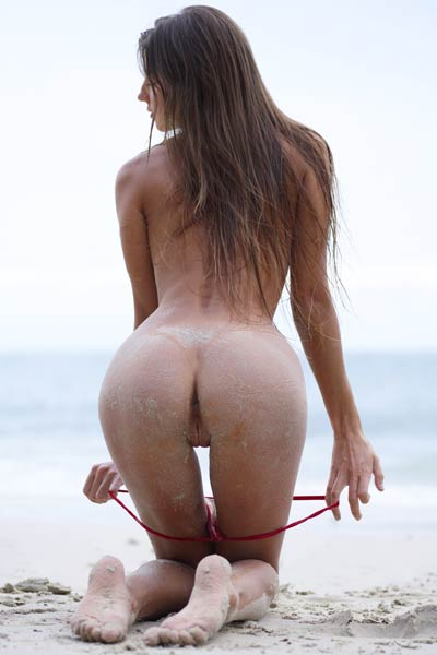 Dazzling babe playfully poses on the beach to show us her sand covered perfect body