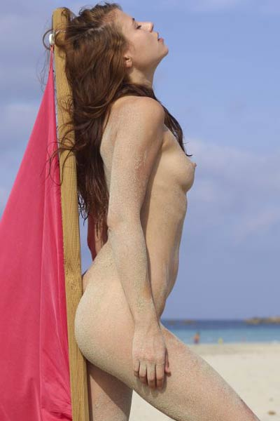 Brunette bombshell seductively poses on the beach with her body covered in sand