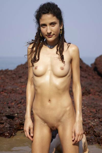 Beautiful brunette Serena L shows her assets by the ocean