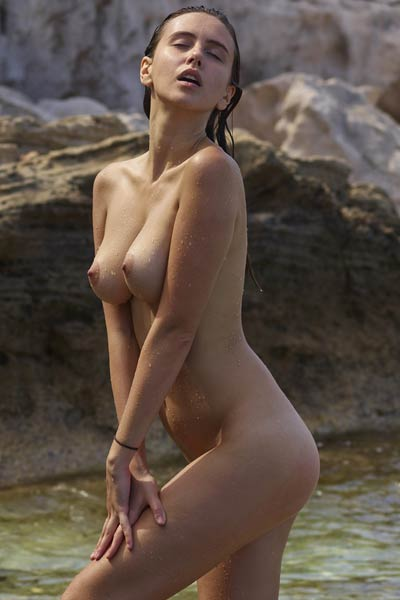 Stunning chick gets nude on the beach baring her nubile body