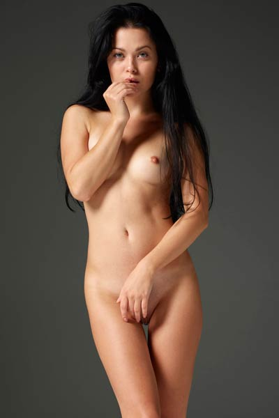 Exotic darkhaired vixen Belle presents her sexy slender body as she poses naked