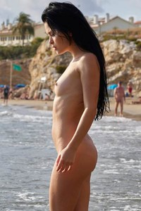 Belle is on her favorite beach flashing with her naked and slim body