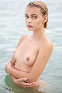Young and beautiful blondie sensually poses naked in the sea