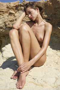 Alluring slender beauty takes off her bodysuit and poses naked on the rocks