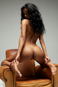 Ebony bombshell Angelique  proudly poses on the leather armchair flaunting her hot curves