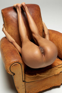 Skinny girl on the leather armchair flashing with her flexible body