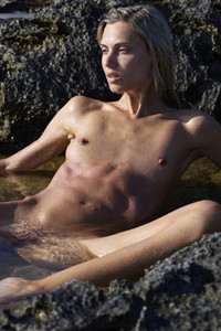 Naked chick sitting in shallow water and showing her small tits and shaved pussy