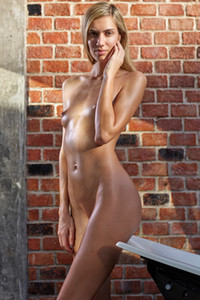 Tall blonde Francy displays her slim body with small tits by the brick wall