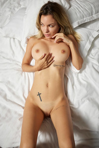Tempting young seductress flaunts her sexy petite body on the bed