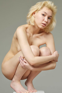 Glorious blonde chick flaunts body and poses naked on a statue stand