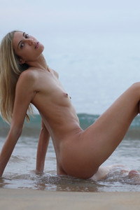 Slim blonde model spreads legs while posing naked on the beach