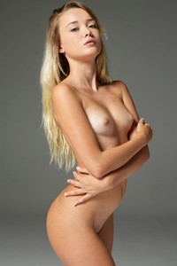 Small titted dame evocatively displaying her sexy body in front of the photographer