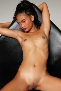 Small titted Asian babe flaunting her naked body as she poses on a chair