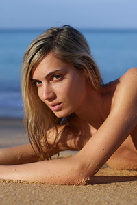 Amazing stunner loves to pose naked on the beach for the camera